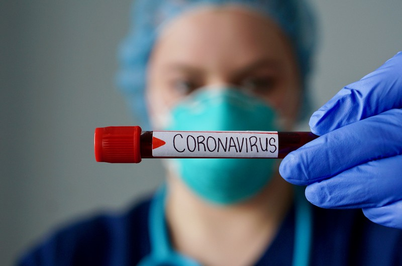 Nurse wearing respirator mask holding a positive blood test result for the new rapidly spreading Coronavirus, originating in Wuhan, China